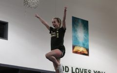 Junior Izzy Ward practicing a stunt for the competition routine.